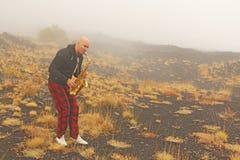 Ein kahler Mann spielt auf einem Goldaltsaxophon in der Natur, gegen lizenzfreie stockfotos