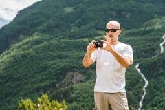 Ein kahler Tourist in der Sonnenbrille an einem Halt macht ein Foto auf seiner Kamera Gegen den Hintergrund von grünen Bergen und Lizenzfreie Stockfotografie