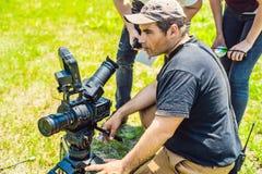Ein Kameramannbetreiber den schießenden Prozess mit einem Direktor und einem DP besprechen lizenzfreies stockfoto
