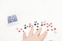 Ein Kartenstapel verbreitet entlang einem weißen Hintergrund Stockbilder