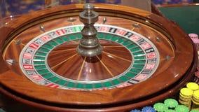 Ein Kasinohändler spinnt Roulettehand stock video footage