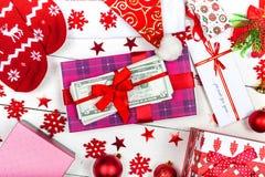 Ein Kasten mit einem Band und ein Stapel Banknoten auf einem weißen backgrou Stockbild
