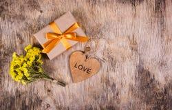 Ein Kasten mit einem Goldband auf einem alten hölzernen Hintergrund Hölzernes Herz und Blumen Kopieren Sie Platz Flache Lage Stockbild