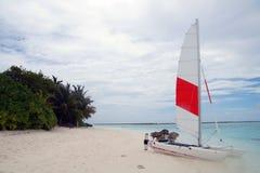 Ein Katamaran mit einem weißen und roten Segel auf dem Strand Stockfoto