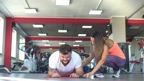 Ein kaukasischer Mann mit einem Bart führt eine Übung in der Turnhallenplanke, folgender schöner Mädchentrainer, Training durch stock video