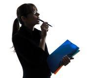 Geschäftsfrau, die Schattenbild oben schauend denkt Stockbild