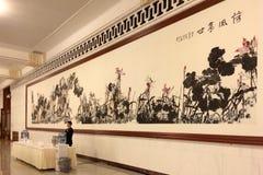 Ein Kellner, der vor einer chinesischen Malerei im Großen Hall von Leuten in Peking steht Lizenzfreie Stockfotos