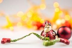 Ein keramischer Weihnachtsmann und ein roter Weihnachtsball Stockbild