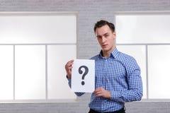 Ein Kerl auf der Seite hält ein Blatt mit einem Fragezeichen Lizenzfreie Stockfotos