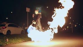 Ein Kerl auf der Stra?e schie?t einen Flammenwerfer nachts Die Flamme belichtet sch?n die Nachtstra?e stock video