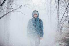 Ein Kerl, der eine Jacke mit einer Haube trägt, steht in einem schneebedeckten Wald, Schnee fällt auf ihn von oben lizenzfreies stockfoto