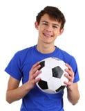 Ein Kerl, der einen Fußball anhält Stockfotografie