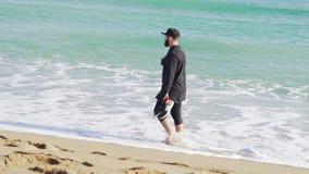 Ein Kerl in der Kleidung gehend auf das Ufer von einem kalten und gewellten Meer in Barcelona stock video