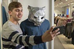 Ein Kerl in einem Bekleidungsgeschäft macht ein lustiges selfie mit einem Mannequin Tiereinkaufen mit einem Telefon in ihren Händ stockfotografie