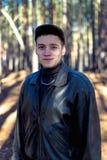 Ein Kerl in einer Lederjacke und in einer Kappe auf einer Straße in einem Kiefernwald lizenzfreie stockbilder