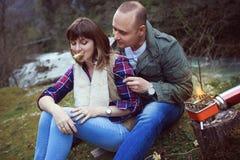 Ein Kerl mit einem Mädchen auf einem Halt im Wald Gebraten auf dem Herd lizenzfreie stockfotos