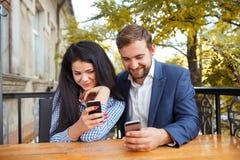 Ein Kerl mit einem Mädchen in einem Café auf der Terrasse sitzen Schulter an Schulter mit Telefonen in den Händen und im Lächeln Stockfotografie