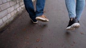 Ein Kerl mit einem Mädchen, das auf den nass Asphalt nach dem Regen geht Nahaufnahme ihrer Füße, die auf den Bürgersteig gehen stock footage