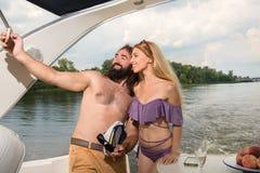 Ein Kerl mit einem Mädchen schießt ein selfie auf einer Yacht stockbilder