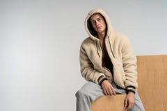 Ein Kerl mit einem nackten Torso in den grauen Hosen, die auf einem hölzernen Würfel sitzen lizenzfreies stockfoto