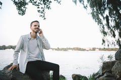 Ein Kerl mit einem Telefon im Park Stockfotografie