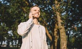 Ein Kerl mit einem Telefon im Park Stockbilder