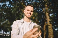 Ein Kerl mit einem Telefon im Park Stockfoto