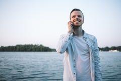 Ein Kerl mit einem Telefon im Park Stockbild