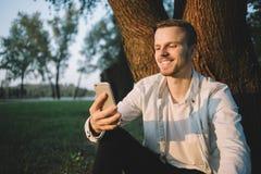 Ein Kerl mit einem Telefon im Park Stockfotos