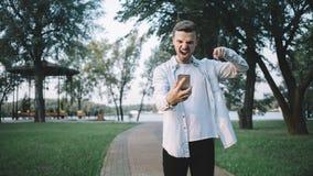 Ein Kerl mit einem Telefon im Park Lizenzfreie Stockfotos
