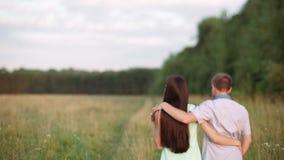 Ein Kerl mit einer Mädchenumfassung geht eine Landstraße zum Feld entlang Sonnenuntergang, Sommer stock footage