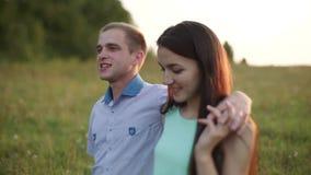 Ein Kerl mit einer Mädchenumfassung geht eine Landstraße zum Feld entlang Sonnenuntergang, Sommer stock video footage