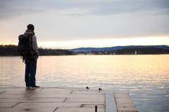 Ein Kerl mit Rucksackblick über dem Meer und dem Träumen vom Reisen lizenzfreies stockbild