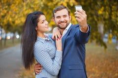 Ein Kerl tut selfie mit einem Mädchen gegen den Hintergrund eines Herbstparks lizenzfreie stockfotos