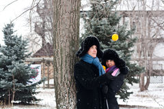 Ein Kerl und ein Mädchen am Baum mit Orange Stockfotografie