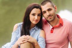 Ein Kerl und ein Mädchen amüsieren sich in einer romantischen Atmosphäre, sitzt auf dem Pier lizenzfreie stockfotos