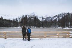 Ein Kerl und ein Mädchen betrachten den gefrorenen See stockfotografie