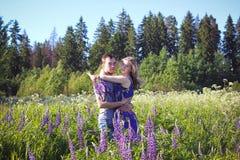 Ein Kerl und ein Mädchen gehen auf dem Gebiet von Lupines Stockbild