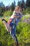 Ein Kerl und ein Mädchen gehen auf dem Gebiet von Lupines Stockfotografie