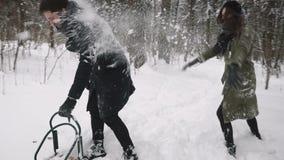 Ein Kerl und ein Mädchen spielen im Schnee im Park Antreiben in einen Schlitten stock footage