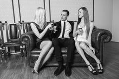 Ein Kerl und zwei Mädchen im Raum Lizenzfreies Stockfoto