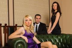 Ein Kerl und zwei Mädchen im Raum Stockbild