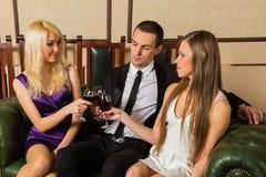Ein Kerl und zwei Mädchen im Raum Stockbilder