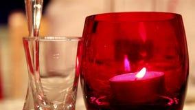 Ein Kerzenlicht innerhalb eines roten Glases und eines kleinen Glases stock video footage
