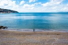 Ein Kind allein, das leeres Meer vom Strand betrachtet stockfoto