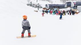 Ein Kind auf einem Snowboard in Sochi, Russland Stockfotos