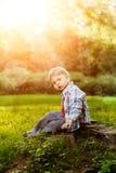 Ein Kind bei Sonnenuntergang, Rücklicht Kind auf der Wiese im Park Th Lizenzfreie Stockbilder