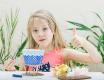 Ein Kind bereitet ein Schokoladenfondue mit Stücken Frucht zu Lizenzfreie Stockbilder