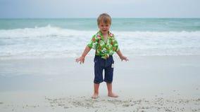 Ein Kind, das auf dem Strandsand am sonnigen Tag spielt Lizenzfreie Stockfotos