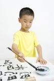 Ein Kind, das chinesische Kalligraphie schreibt stockbild